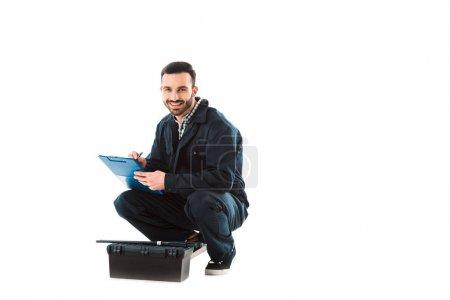 Foto de Alegre obrero escribiendo en el portapapeles mientras se sienta cerca de la caja de herramientas y mirando la cámara aislada en blanco - Imagen libre de derechos