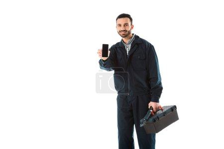Photo pour Bricoleur souriant avec le smartphone de fixation de boîte à outils avec l'écran blanc d'isolement sur le blanc - image libre de droit