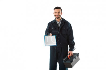 Foto de Smiling handsome workman with toolbox holding blank clipboard isolated on white - Imagen libre de derechos