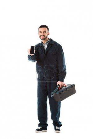 Photo for Cheerful handyman with toolbox holding smartphone with blank screen and looking at camera isolated on white - Royalty Free Image
