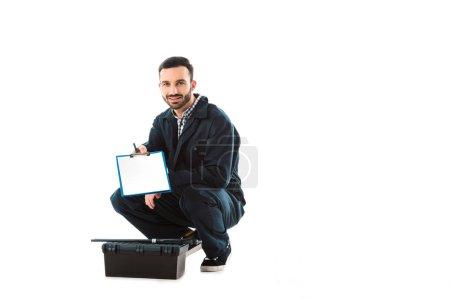 beau plombier souriant tenant presse-papiers avec du papier blanc tout en étant assis près de la boîte à outils isolé sur blanc