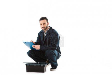 Foto de Reparador serio escribir en el portapapeles mientras está sentado cerca de la caja de herramientas y mirando la cámara aislada en blanco - Imagen libre de derechos