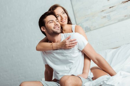Photo pour Femme heureux étreignant le petit ami beau dans la chambre à coucher - image libre de droit