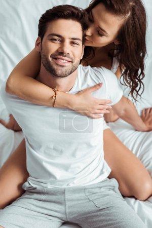 Photo pour Vue aérienne de la femme embrassant la joue du petit ami heureux dans la chambre à coucher - image libre de droit