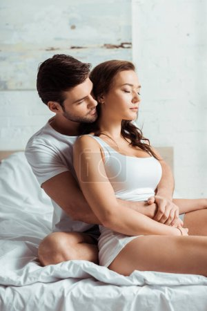 Photo for Handsome man hugging attractive girlfriend with closed eyes - Royalty Free Image
