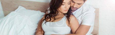 Photo pour Plan panoramique de l'homme étreignant femme attrayante tout en étant couché sur le lit - image libre de droit