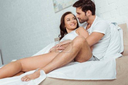 Photo pour Bel homme se trouvant sur le lit avec la petite amie heureuse dans la chambre à coucher - image libre de droit