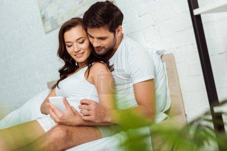 Photo pour Foyer sélectif de femme heureuse en utilisant smartphone près de bel homme - image libre de droit