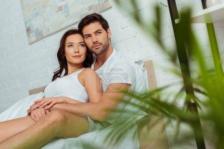 Photo pour Foyer sélectif de l'homme beau se trouvant dans le lit avec la femme attirante - image libre de droit