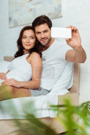 Photo pour Foyer sélectif de l'homme beau prenant le selfie avec la petite amie attrayante dans la chambre à coucher - image libre de droit