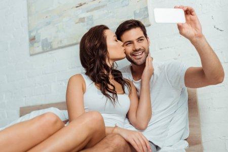 Photo pour Petite amie attirante embrassant la joue du petit ami heureux prenant le selfie sur le smartphone - image libre de droit