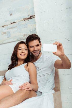 Photo pour Homme heureux souriant près de la petite amie attirante tout en prenant le selfie - image libre de droit