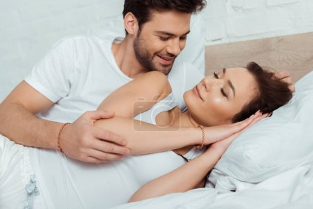 Photo for Happy man looking at attractive girl lying on bed with closed eyes - Royalty Free Image