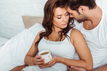 Photo for Handsome man near attractive woman holding cup of coffee in bed - Royalty Free Image