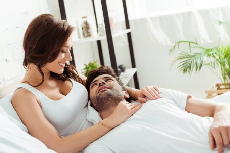 Photo for Happy girlfriend looking at boyfriend lying on bed - Royalty Free Image