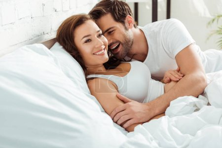 Photo for Happy man smiling while looking at attractive girlfriend in bed - Royalty Free Image