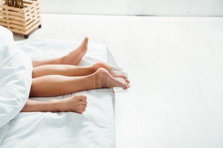 Photo pour Vue recadrée de pieds nus sur la petite amie et le petit ami se trouvant sur le lit - image libre de droit