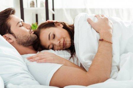 Photo pour Belle femme se trouvant sous la couverture près de l'homme beau dans le lit - image libre de droit