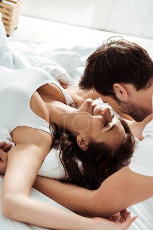 Photo pour Petit ami près de la petite amie heureuse avec les yeux fermés se trouvant sur le lit - image libre de droit