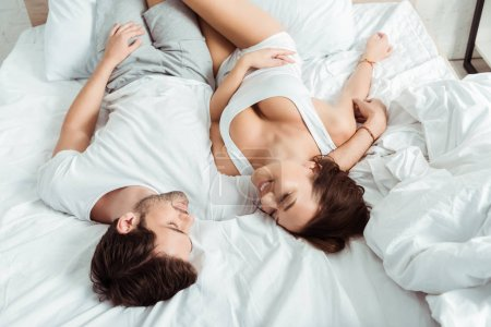 Photo for Happy girlfriend and cheerful boyfriend lying on bed and looking at each other - Royalty Free Image