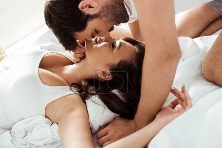 Photo pour Bel homme avec les yeux fermés près de petite amie attrayante sur le lit - image libre de droit