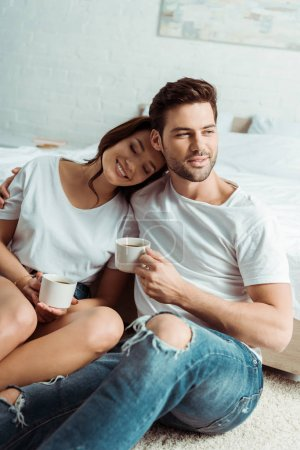Photo for Handsome man and cheerful woman holding cups in bedroom - Royalty Free Image