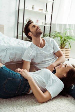 Photo pour Femme heureux regardant le sourire bel homme tout en s'asseyant sur le tapis - image libre de droit