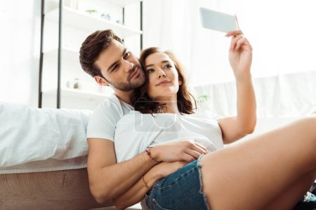 Photo for Low angle view of man and woman taking selfie in bedroom - Royalty Free Image