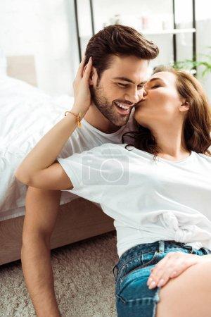 Photo pour Petite amie embrassant la joue du petit ami heureux dans la chambre à coucher - image libre de droit