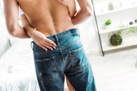 Photo pour Vue arrière de l'homme musculaire restant dans des jeans près de la petite amie dans la chambre à coucher - image libre de droit
