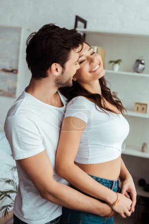 Photo for Happy man hugging cheerful girl in white t-shirt standing at home - Royalty Free Image