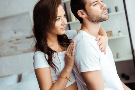 Photo for Attractive girl hugging handsome man standing in white t-shirt at home - Royalty Free Image