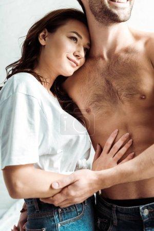 Photo pour Foyer sélectif de fille heureuse touchant torse nu petit ami à la maison - image libre de droit