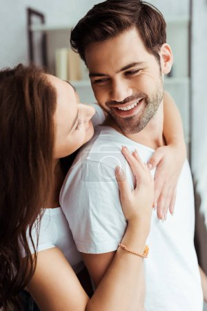 Photo for Beautiful girl hugging happy man standing in white t-shirt at home - Royalty Free Image