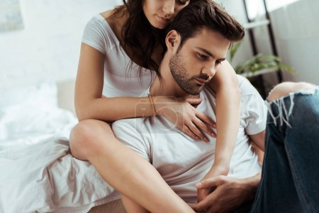 Photo for Cropped view of woman sitting on bed and hugging handsome man - Royalty Free Image