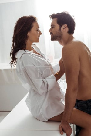 Photo for Happy pretty girl touching shirtless and muscular boyfriend - Royalty Free Image
