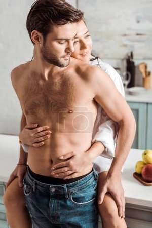 Photo pour Gai et jolie fille embrassant l'homme musculaire beau dans la cuisine - image libre de droit