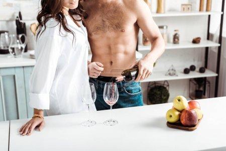 Photo pour Vue recadrée de l'homme torse nu versant le vin rouge dans le verre de vin près de la fille dans la cuisine - image libre de droit
