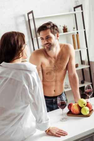 Photo for Shirtless and handsome man looking at brunette girl in kitchen - Royalty Free Image