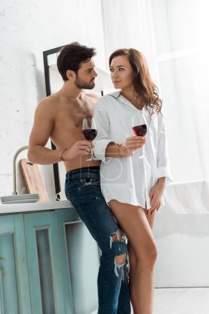 Photo for Low angle view of handsome shirtless man holding wine glass and looking at brunette woman in kitchen - Royalty Free Image