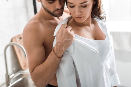 Photo for Muscular man undressing brunette pretty girl with closed eyes - Royalty Free Image