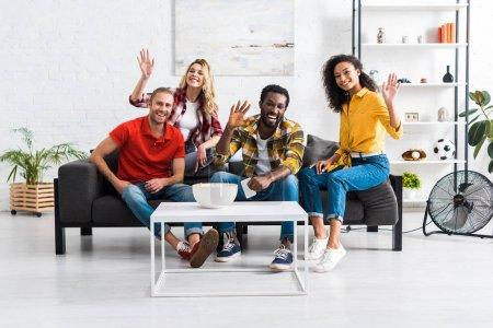 Foto de Amigos multiculturales sonrientes están sentados en el sofá, agitando las manos y divirtiéndose juntos - Imagen libre de derechos