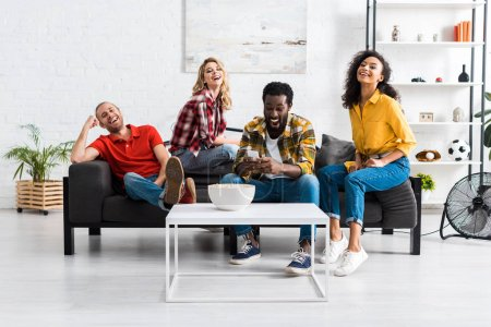 Photo for Exited and happy multicultural young men and women sitting on couch and having fun together - Royalty Free Image