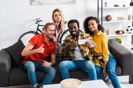 Photo pour Excited happy multicultural men and women sitting on couch and taking selfie in living room - image libre de droit