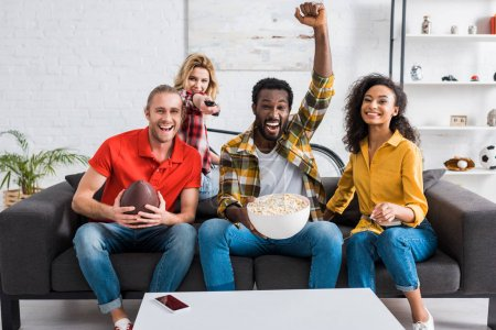 Photo pour Happy multicultural friends sitting on couch and watching championship near table with popcorn in bowl - image libre de droit