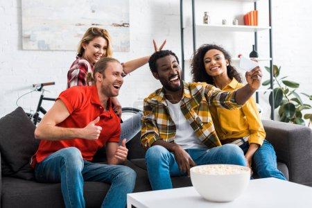 Foto de Positivo feliz amigos multiétnicos tomando selfie y divirtiéndose en casa - Imagen libre de derechos