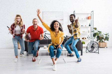 Photo pour Amis multiculturels riants se réjouissant dans le salon à la maison - image libre de droit