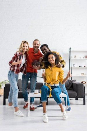 Photo pour Quatre amis multiculturels heureux et souriants passant le temps ensemble à la maison - image libre de droit