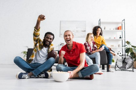 Photo for Happy and positive multicultural young people sitting on floor and watching sport game with bowl of popcorn - Royalty Free Image