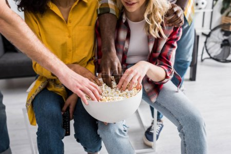 Photo for Cropped view of four multicultural friends with bowl of popcorn in living room - Royalty Free Image